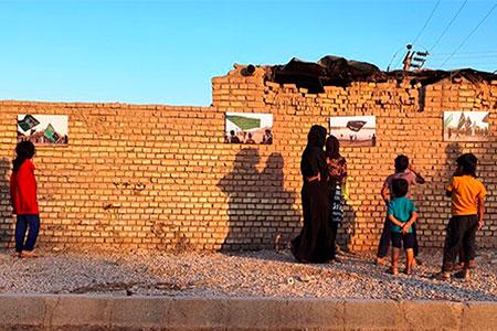 قابهای نمایشگاه عکس «حنین الاربعین» روی دیوار خانههای روستایی